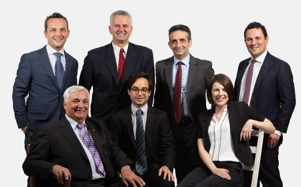 6 men and 1 woman wearing business suits smiling