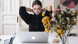 Female sitting at desk in front of laptop with arms raised behind neck